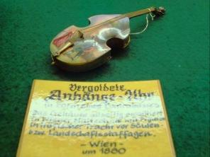 Uhrenmuseum Wuppertal vergoldete Anhänge-Uhr (Armbanduhr) in Form einer historischen Violine bemalter Decke Schild in Schauvitrine : … Wien 1880 © noten-apitz.de; Bildquelle: Musikverlag Apitz